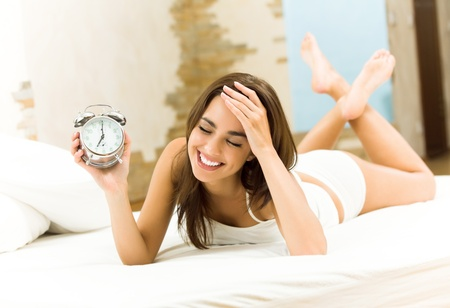 Young woman with alarmclock on the bed at the morning Stock Photo - 12995662