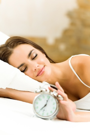 Portrait of young beautiful woman with alarmclock lying on bed, at home photo
