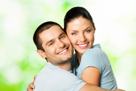 Portrait of young happy smiling cheerful attractive amorous couple, outdoors photo