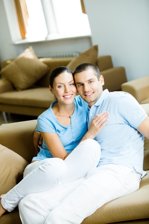 Portrait of young happy smiling attractive cheerful couple at home photo