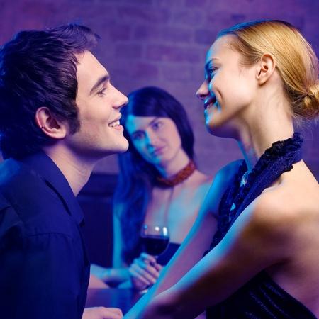 celos: Pareja joven sonriente feliz y una mujer mirando a ellos en el club. Conc�ntrese en pareja.