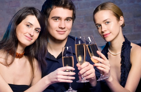 Two young beautiful women and man with champagne at party  photo
