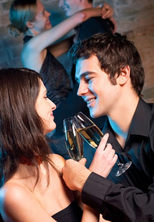 Young happy amorous couple with glasses of champagne on romantic date at restaurant or club photo