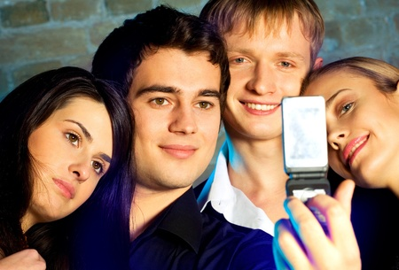 Young happy smiling cheerful people taking photograph by cellphone at party photo
