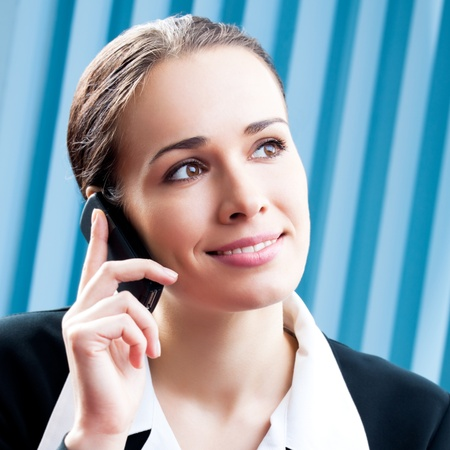 Happy smiling cheerful young business woman with cellphone at office photo