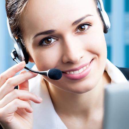 recepcionista: Retrato de feliz y sonriente operador de tel�fono de soporte alegre en el auricular en la oficina