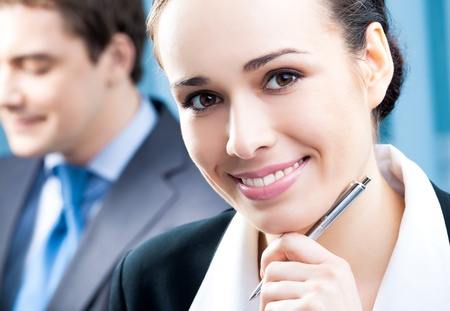 Portrait of happy smiling cheerful young businesswoman with colleague on background, at office Stock Photo - 13319256