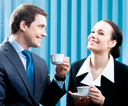 Two happy smiling cheerful business people with coffee at office photo