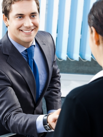 handshaking: Two happy smiling cheerful businesspeople or business man and client handshaking at office Stock Photo