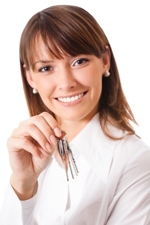 Young happy smiling business woman or real estate agent showing keys from new house, isolated over white background. Focus on keys. Stock Photo - 13532236