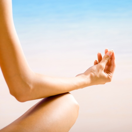 Young beautiful woman doing yoga exercises or meditating on beach photo
