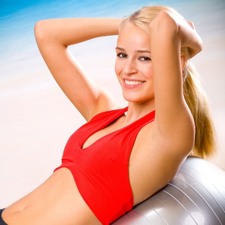 Young happy woman doing fitness exercises with pilates gym ball on beach Stock Photo - 13532345