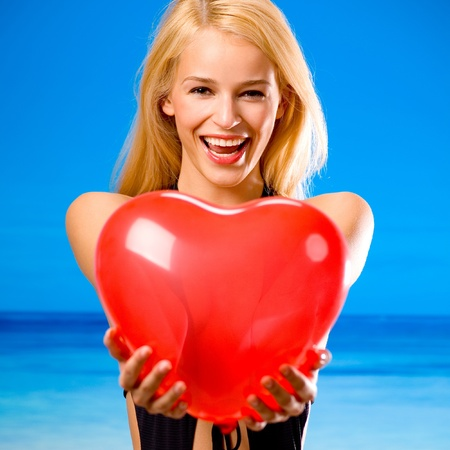 Young beautiful happy smiling cheerful blond woman on beach, holding valentine's balloon Stock Photo - 13532315
