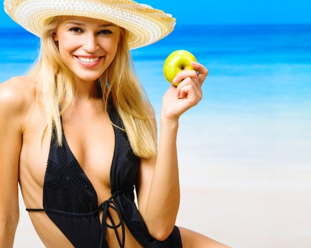 swimwear: Young happy smiling cherful beautiful woman with apple on beach
