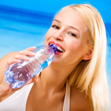 water activity: Portrait of beautiful happy woman with bottle of water on beach Stock Photo