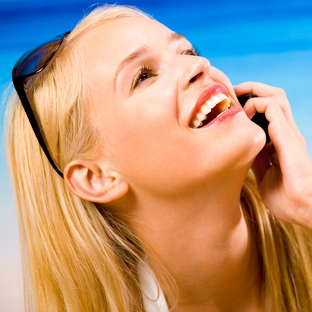 Portrait of beautiful happy smiling cheerful young woman with cell phone on beach photo