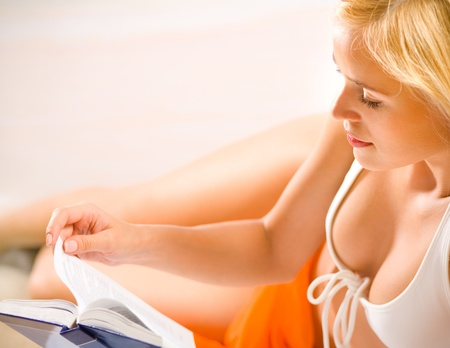 Young beautiful blond woman in bikini, reading book on beach photo