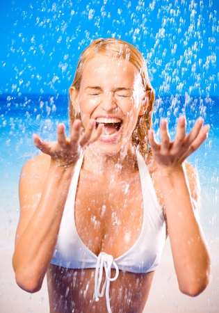 Young beautiful happy tanned blond woman in bikini at rain or summer shower on beach photo