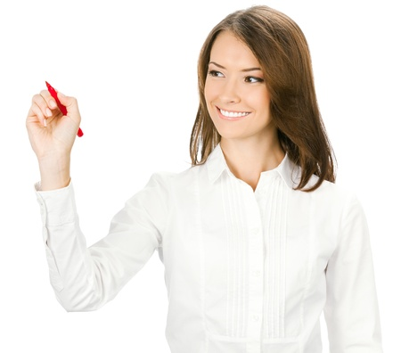 Happy smiling cheerful young business woman writing or drawing something on screen with red marker, isolated on white background photo