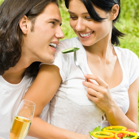 Young happy smiling cheerful couple with champagne and fruits at picnic, outdoors photo