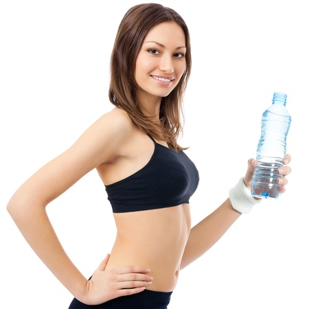 Happy smiling young woman in fitness wear with bottle of water, isolated over white background photo