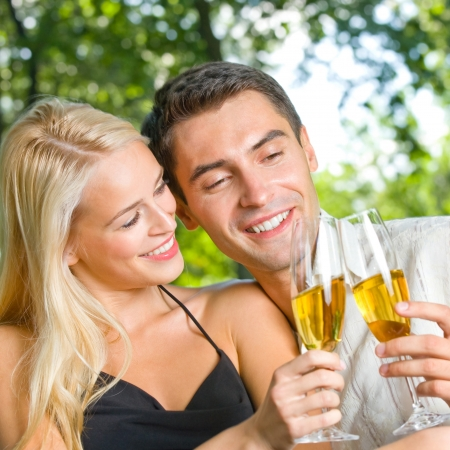 Young happy smiling cheerful attractive couple celebrating with glasses of champagne, outdoor photo