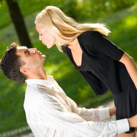 enamorados besandose: Joven besos feliz pareja amorosa, al aire libre Foto de archivo