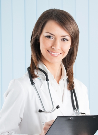 Portrait of happy young smiling female doctor with clipboard at office photo