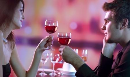 jovenes tomando alcohol: Joven pareja feliz amorosa con vasos de vino tinto en la cita rom�ntica en el restaurante