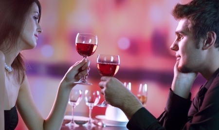 Young happy amorous couple with glasses of redwine on romantic date at restaurant photo