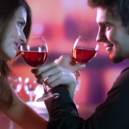 Young happy amorous couple with glasses of redwine on romantic date at restaurant Stock Photo - 14158645