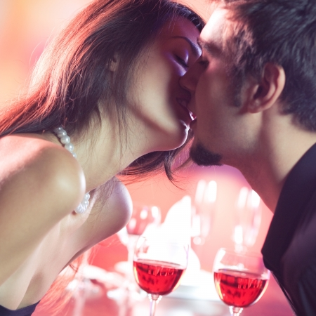 Young happy amorous couple kissing on romantic date, at restaurant photo