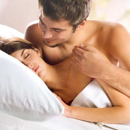 sexo cama: Pareja joven hermosa amorosa en el dormitorio Foto de archivo
