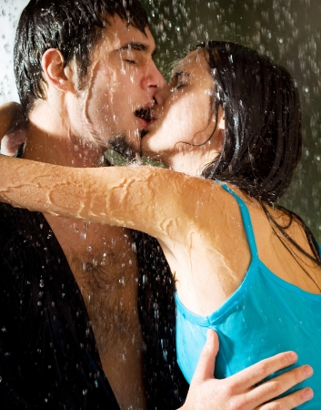 Young happy amorous couple hugging and kissing under a rain, outdoors Stock Photo - 14152050