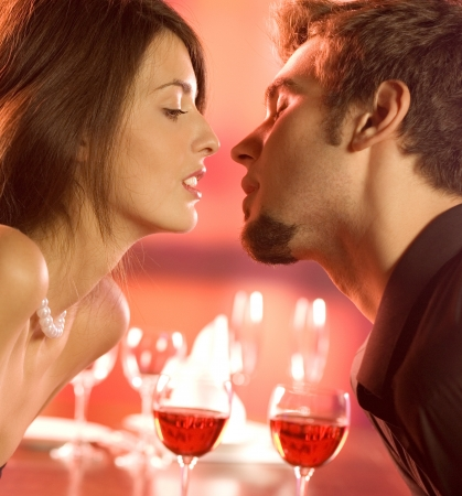Young happy amorous couple kissing on romantic date, at restaurant Stock Photo - 14158705
