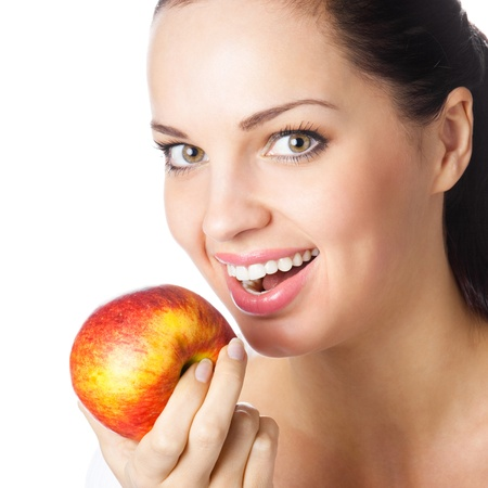 Portrait of young attractive happy smiling woman eating apple, isolated over white background photo