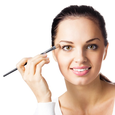 Portrait of young happy smiling woman applying eye shadow, by visage brush, isolated over white background photo