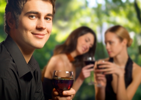 Young happy smiling man with a glass of red wine celebrating at restaurant, bar or cafe photo