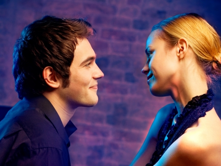 Young happy amorous attractive couple looking at each other, at club photo