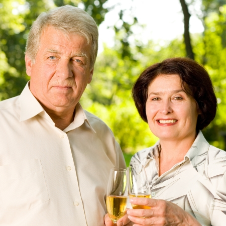 Happy attractive senior couple celebrating together with champagne, outdoors photo