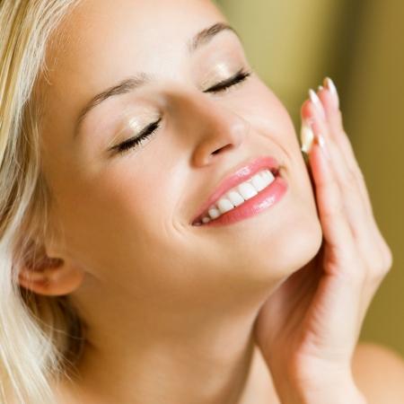 mujer maquillandose: Retrato de joven sonriente feliz alegre hermosa mujer rubia la aplicación de crema, en el hogar
