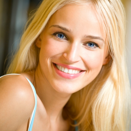 indoors: Portrait of happy cheerful smiling young beautiful blond woman, indoors Stock Photo
