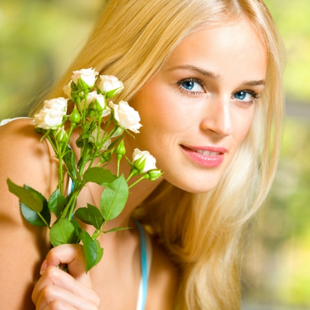 Young happy smiling cheerful woman with bouquet of white roses photo