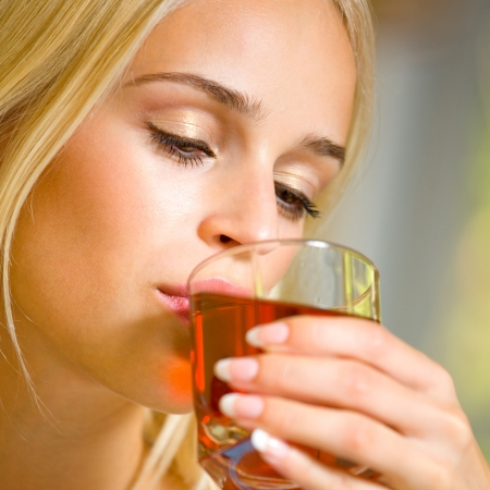 Portrait of happy smiling young beautiful blond woman drinking garnet juice photo