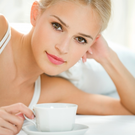Happy smiling beautiful blond woman awaking with cup of coffee at bedroom photo