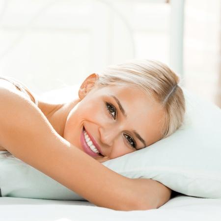 despertarse: Hermosa joven rubia mujer sonriente feliz despertar en la cama