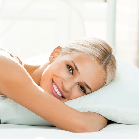 1 woman only: Young beautiful happy smiling blond woman waking up on bed