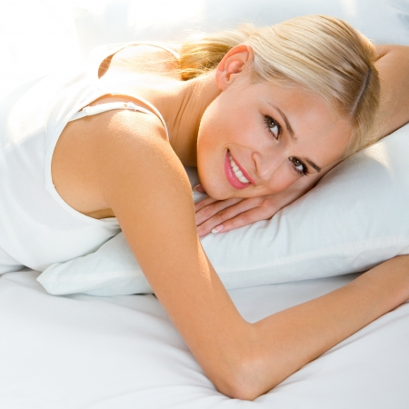 up wake: Young beautiful happy smiling blond woman waking up on bed
