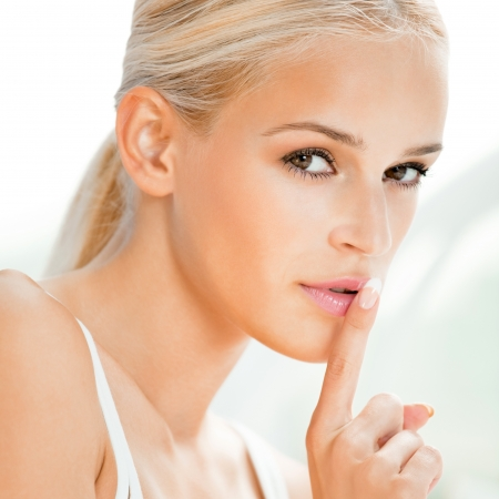 guardar silencio: Retrato de mujer rubia hermosa con el dedo en los labios