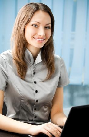 trabajo social: Joven alegre, sonriente mujer de negocios que trabajan con el port�til en la oficina